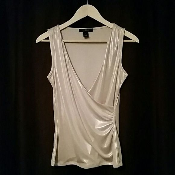 "White House Black Market shirt size S This light metallic gold top by WHBM is perfect to wear for your night out on the town with a pair of jeans, layered under a blazer for a sharp look.  97% polyester, 3% Spandex.  24"" Length.  15"" Bust.  Never worn. White House Black Market Tops Tank Tops"