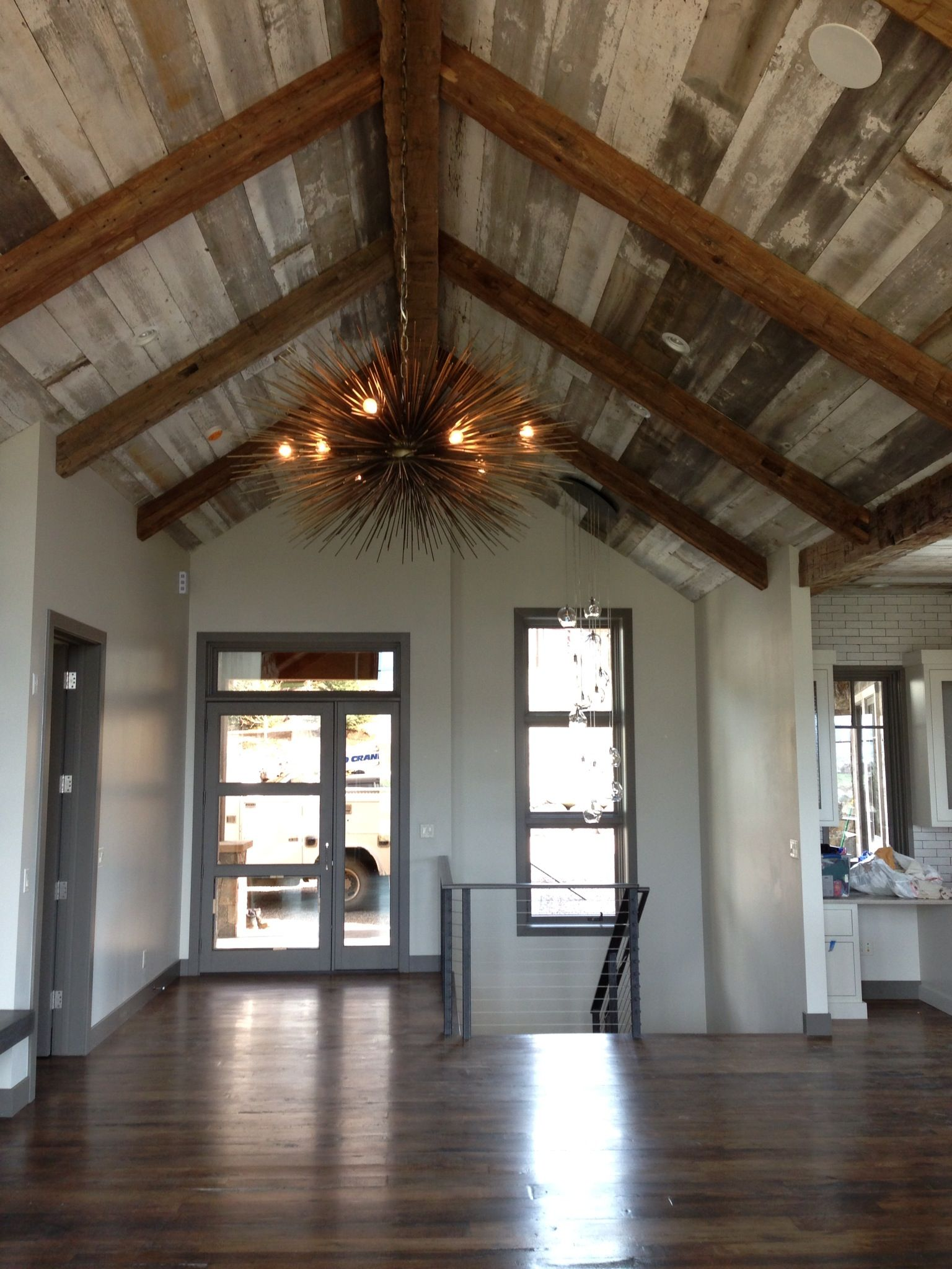 Hand hewn beams and white grey barn board adorn this for Architectural beams