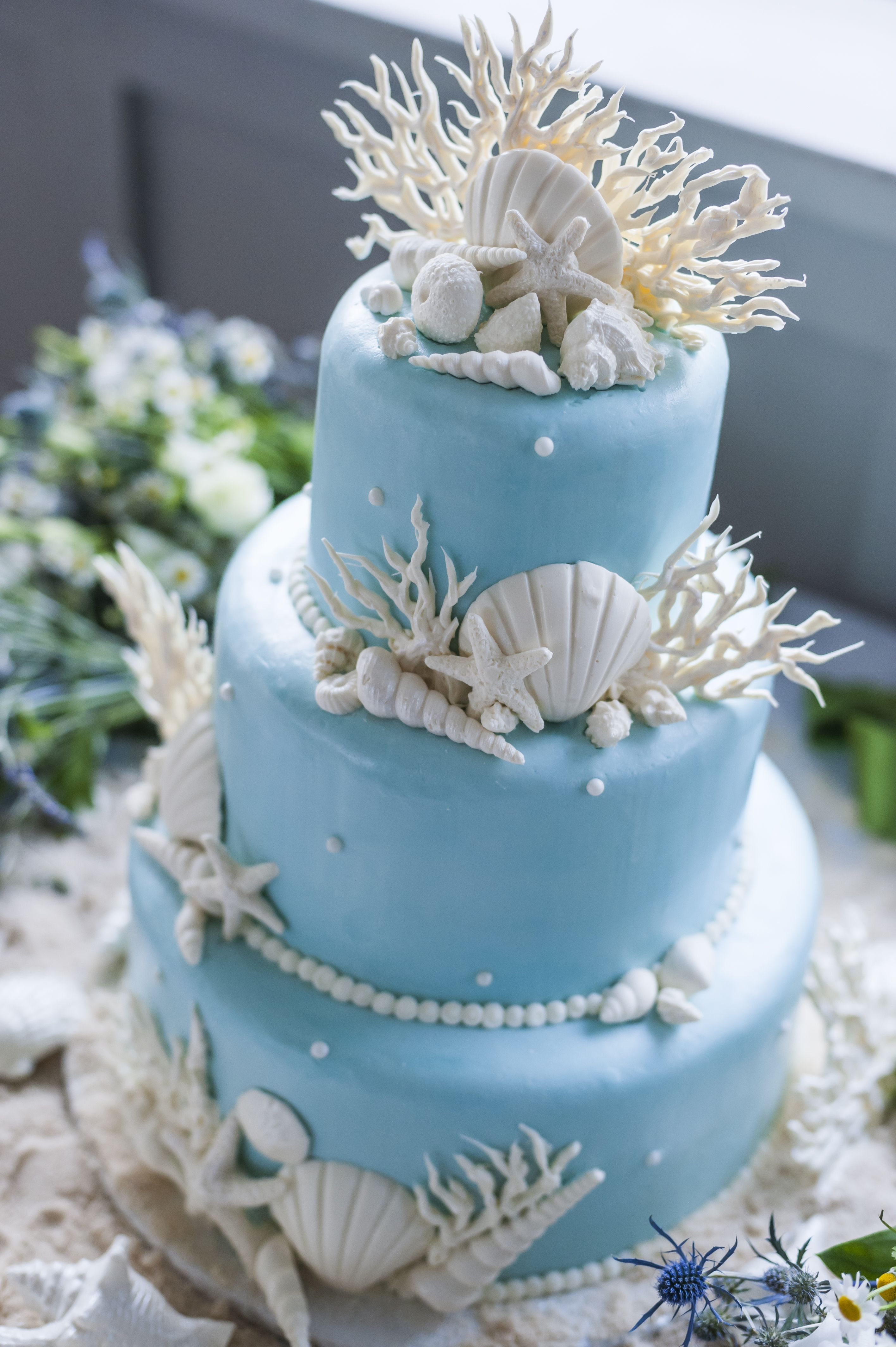 White Seashell And Coral Decorated Blue Wedding Cake Beach Wedding Cake Beach Theme Wedding Cakes Themed Wedding Cakes