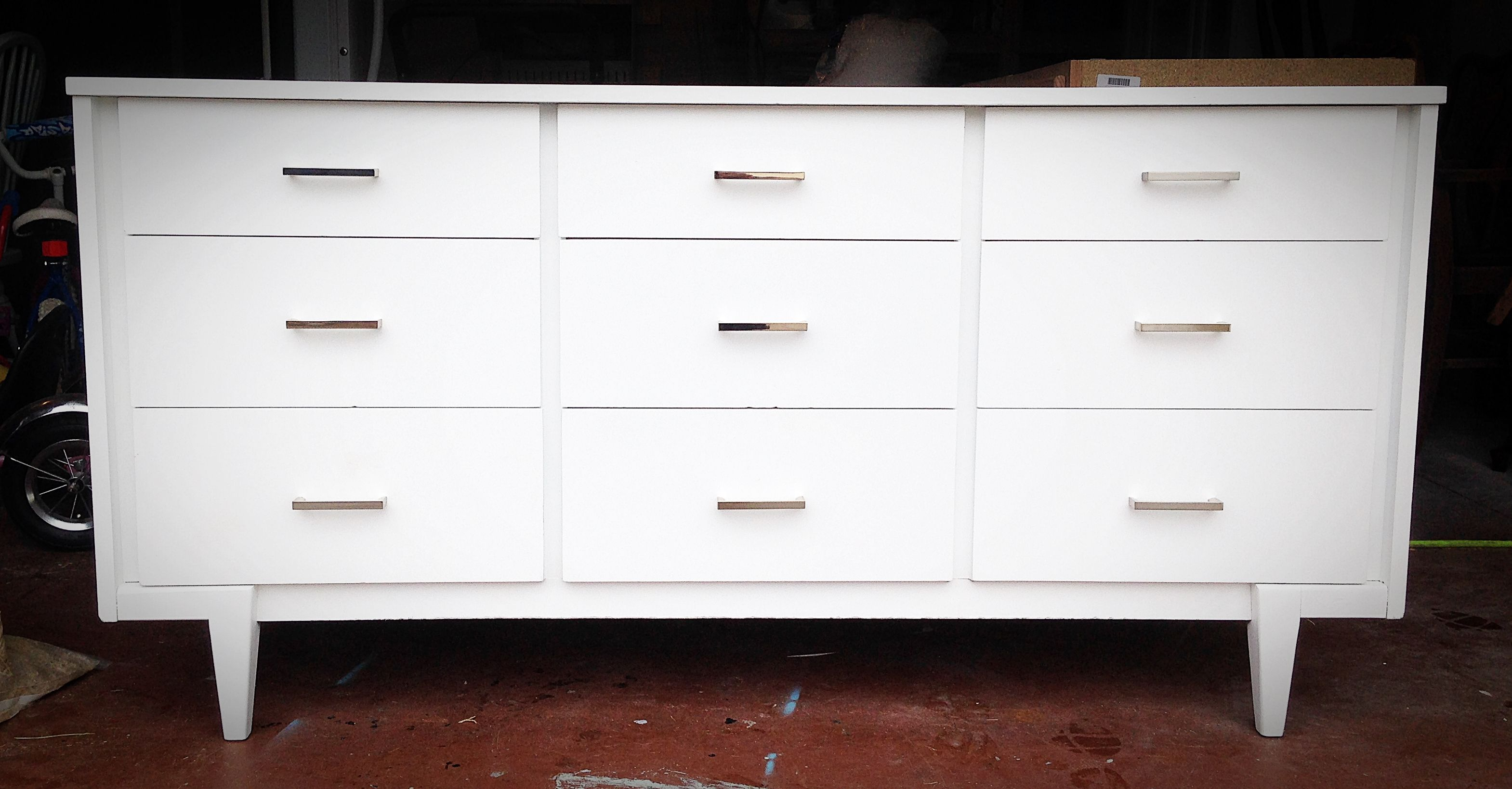 midcentury modern dresser painted with sherwin williams pure white and updated with chrome drawer