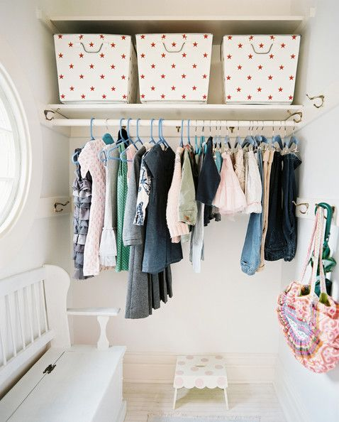 Quirky closet organization with a polka-dotted stool and a white bench