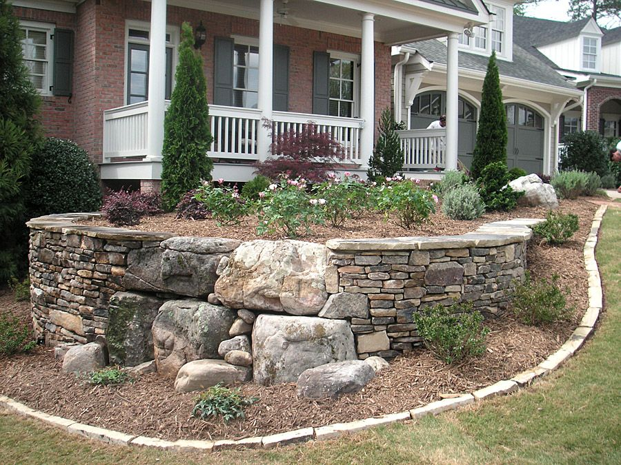 Large rocks adds interest to the stacked slate retainer for Large landscaping stones