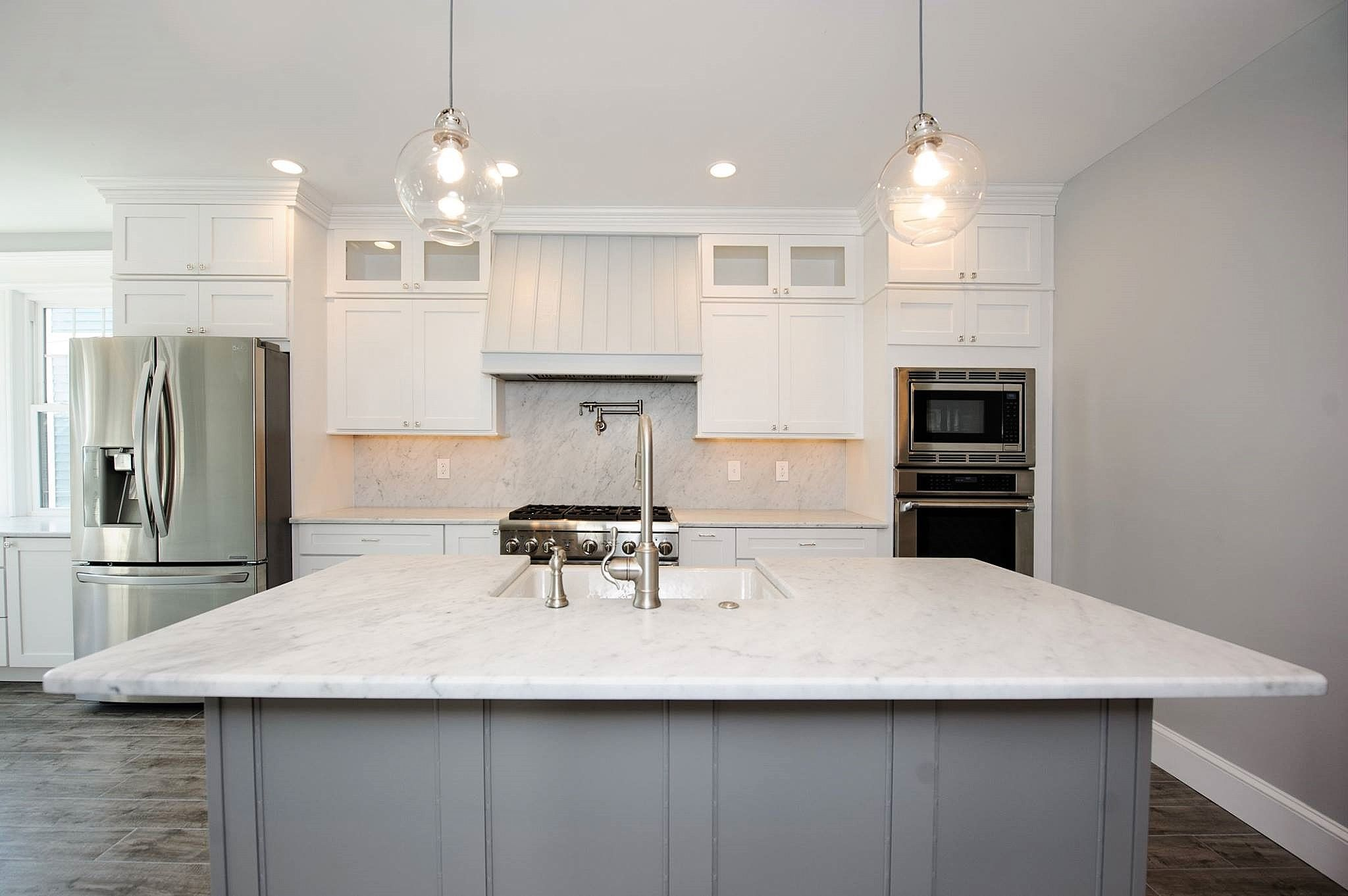 This Bright And Airy Shore Home Features Stunning Honed Carrara Marble Countertops With A Full Height Marble Countertops Countertops Natural Stone Countertops
