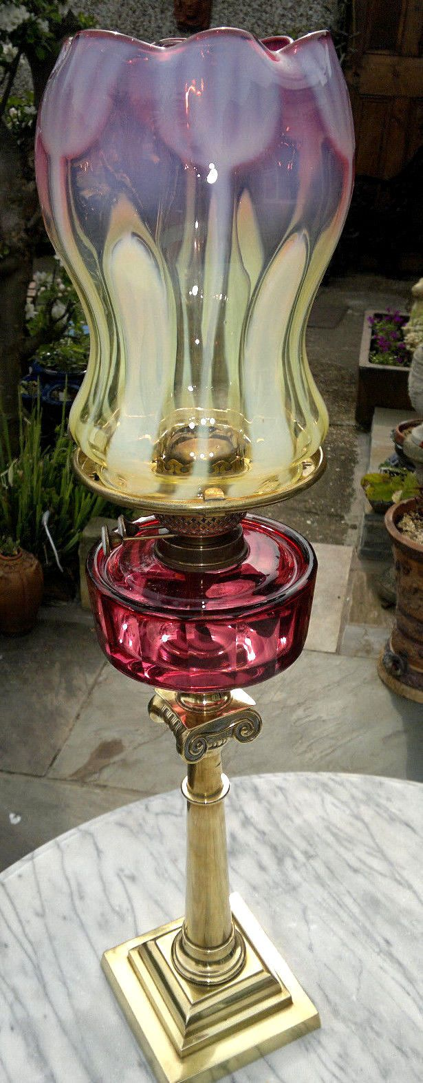 Rare Antique Victorian Art Nouveau Vaseline & Cranberry Glass Oil Lamp Art. Has a stunning vaseline uranium and cranberry glass shade with a faceted cut cranberry glass font standing on a brass square footed tapered ionic column base. It is in working order with the glass shade and font in excellent.