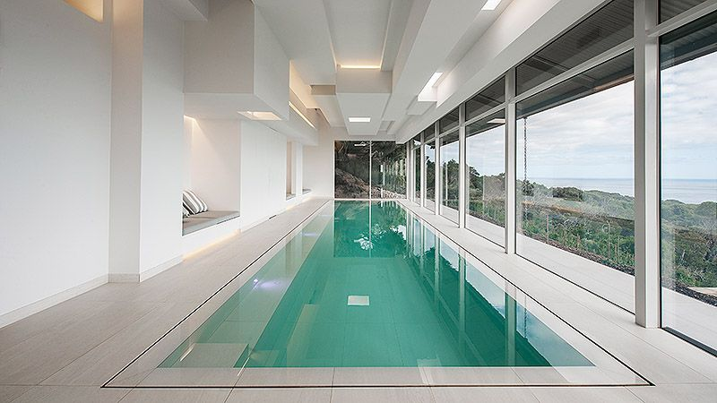 Indoor lap pool with wet edge. Love the large format pool tile. Pinned to Pool Design by Darin Bradbury.