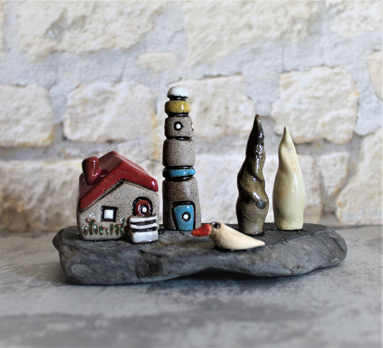 Ceramic sculpture of a gray clay beach house lighthouse