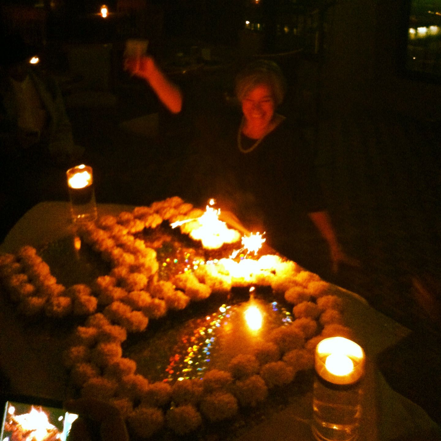 50th Birthday Celebration Floating Candles Sparkling And Lots Of Cupcakes Displayed In The Number 50