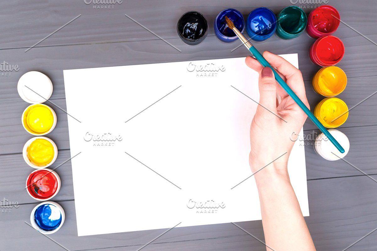 Photo of Hand holds brush over sheet #Sponsored , #Ad, #sheet#blank#paper#white