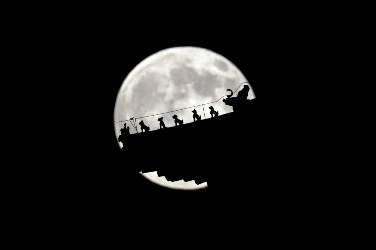 A supermoon rises behind figurines on a Chinese pavilion in Beijing, China, July 12, 2014 - AP Photo/Ng Han Guan
