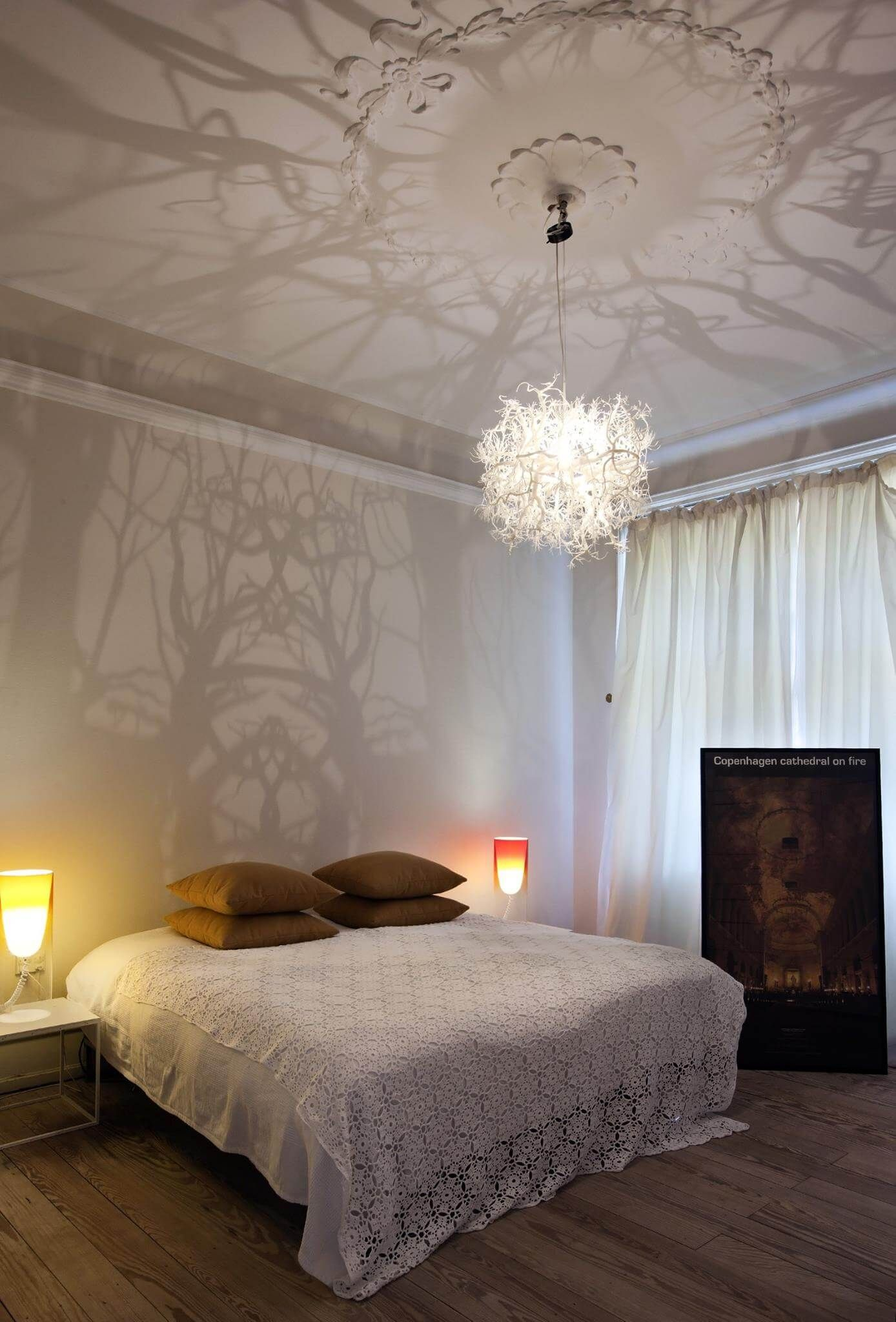 Intricate Chandelier Casts Mysterious Forest Scene on Walls