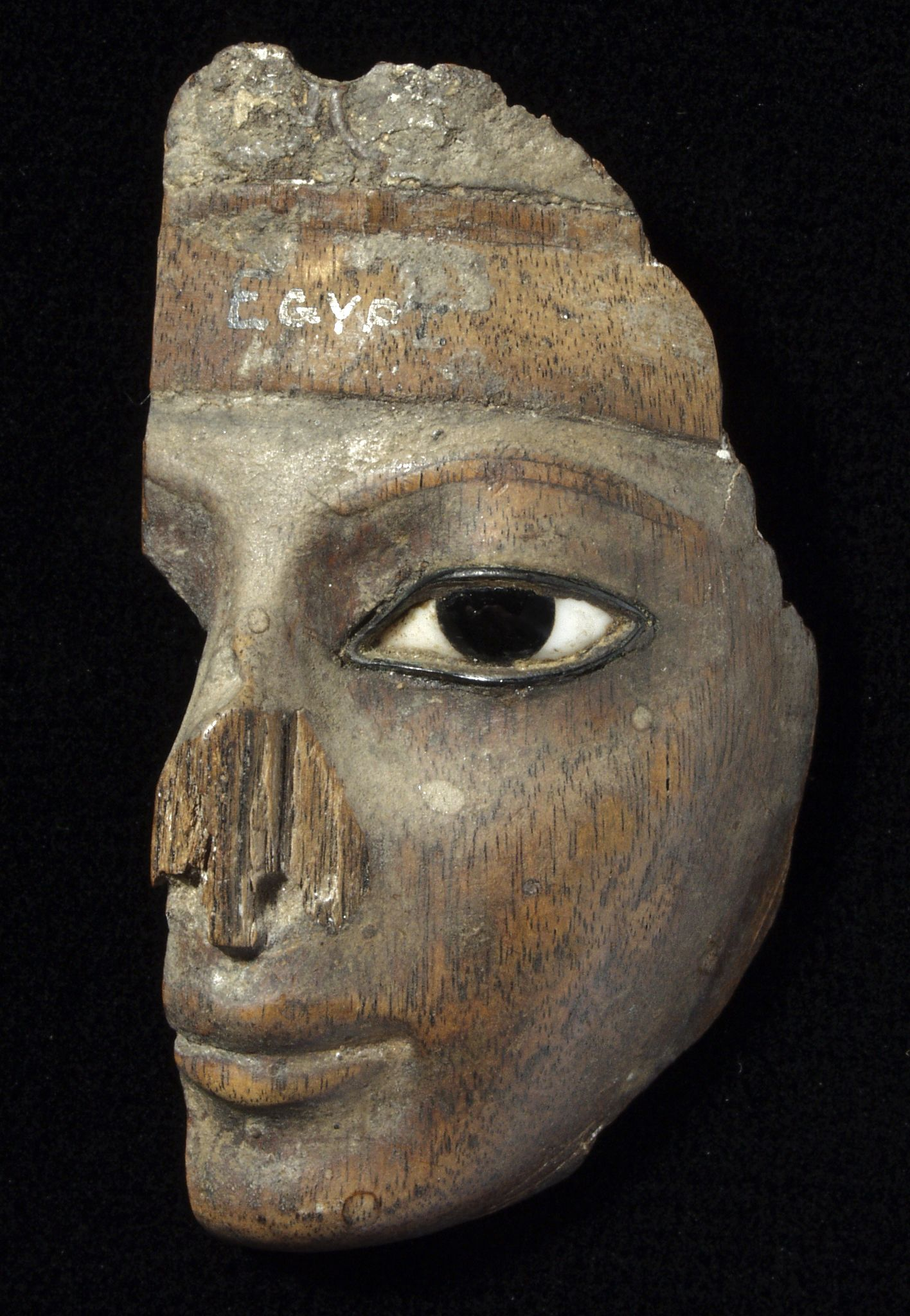 Fragment of a carved wooden face with an inlaid, socketed eye. Egypt. (1884.67.19)