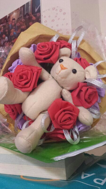 Handmade teddy bear dipping into a bouquet of handmade roses..