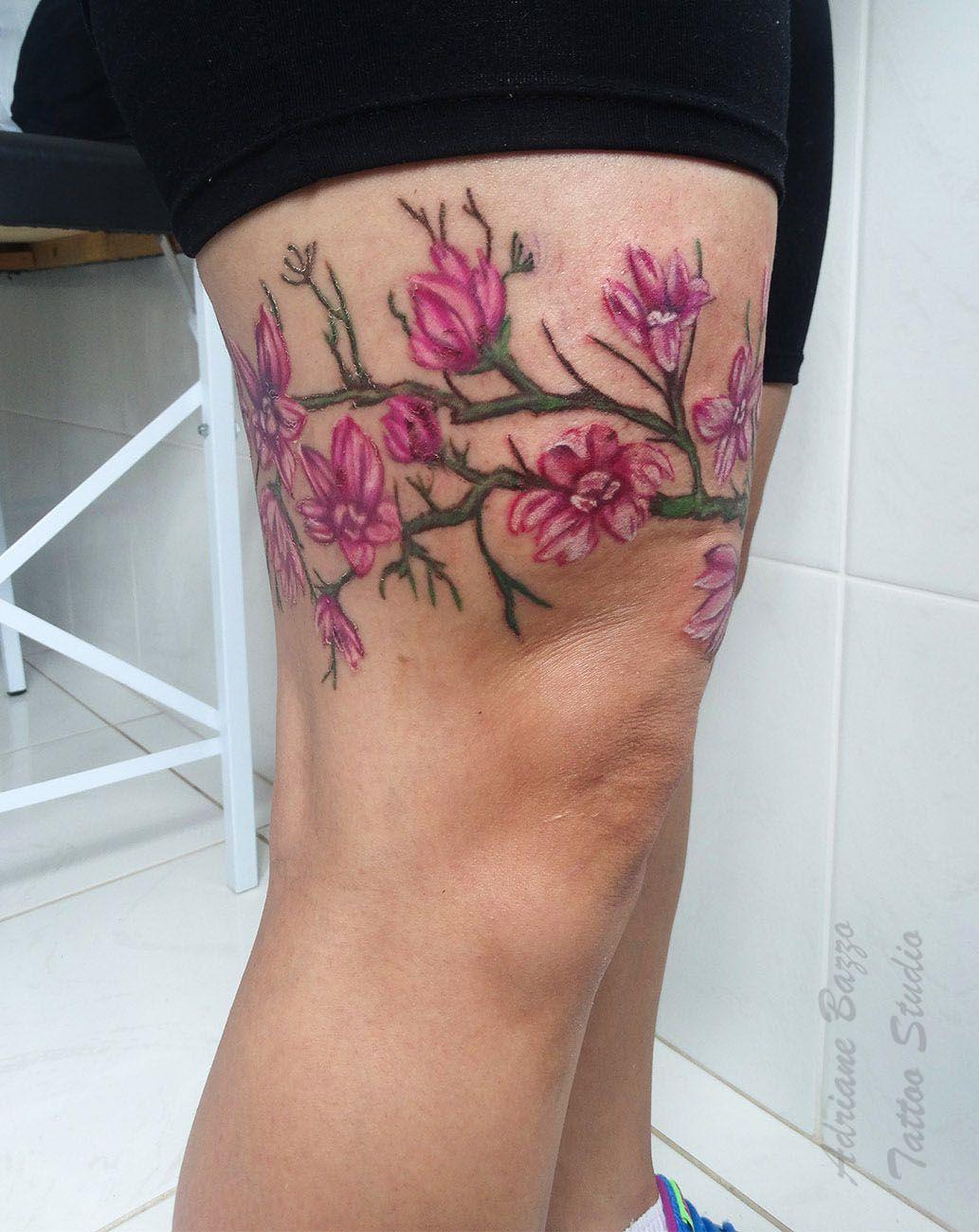 Tatuagem colorida de cerejeira na coxa Adriane Bazzo