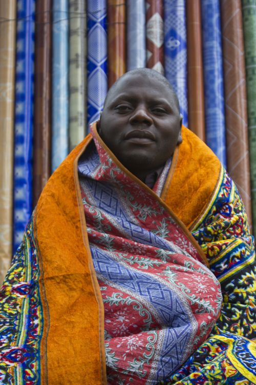 """typicalugandan:  A rug salesman keeps warm by his product, Owino Market, Kampala, Uganda Photography by   Rory Mizen   """