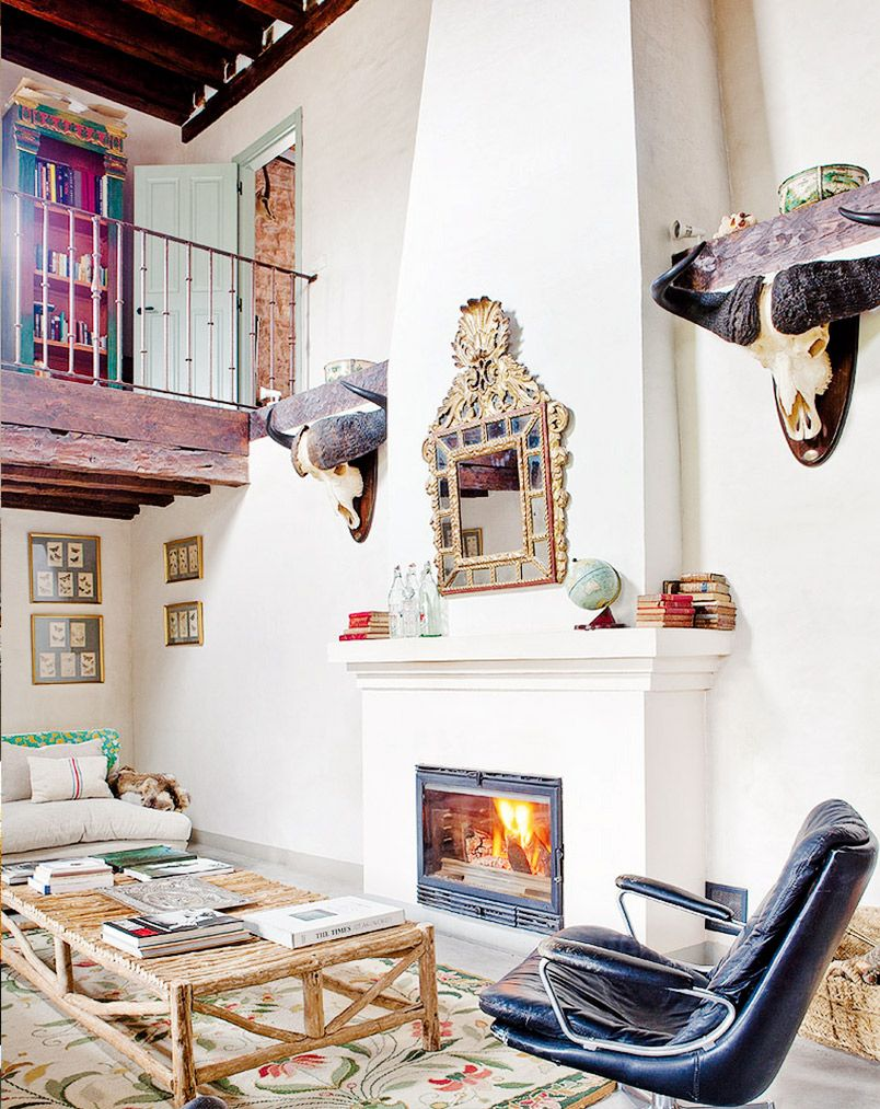 White and wood living room with Spanish details and a fireplace