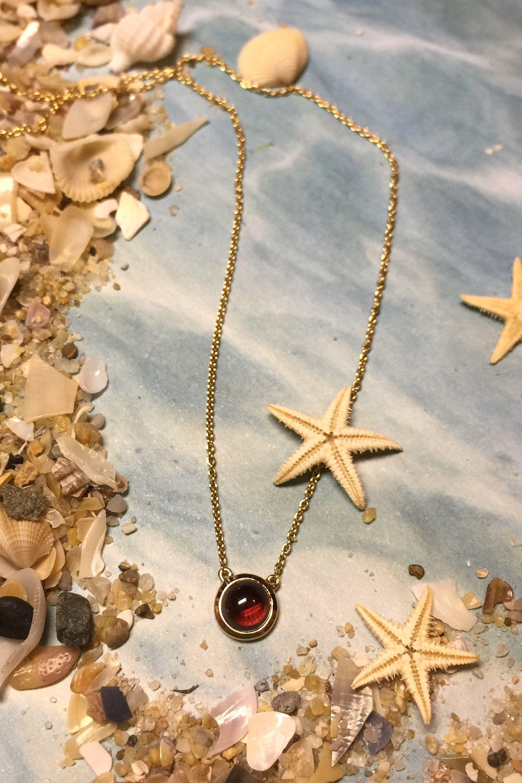 Simple bezel set garnet cabochon gold pendant pemba jewellery