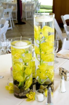 Submerged flowers.  I would like to do this in a shorter container. I don't want my guest to play peek-a-boo around the decorations.