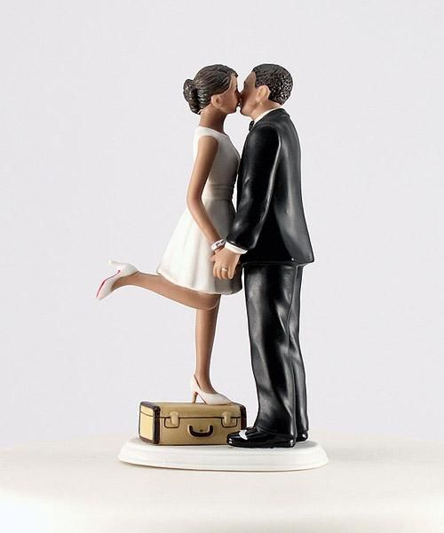 """A Kiss and We're Off!"" Hispanic Couple Wedding Cake Topper made of hand painted porcelain.  The bride is wearing a short white dress, white shoes, and she is standing on top of a suitcase. The groom is wearing a handsome black suit, holding his bride's hands, stealing a kiss from her before they run off on their honeymoon."