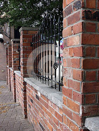 Brick and wrought iron fence decorated with arrowheads on for Brick and wrought iron fence designs