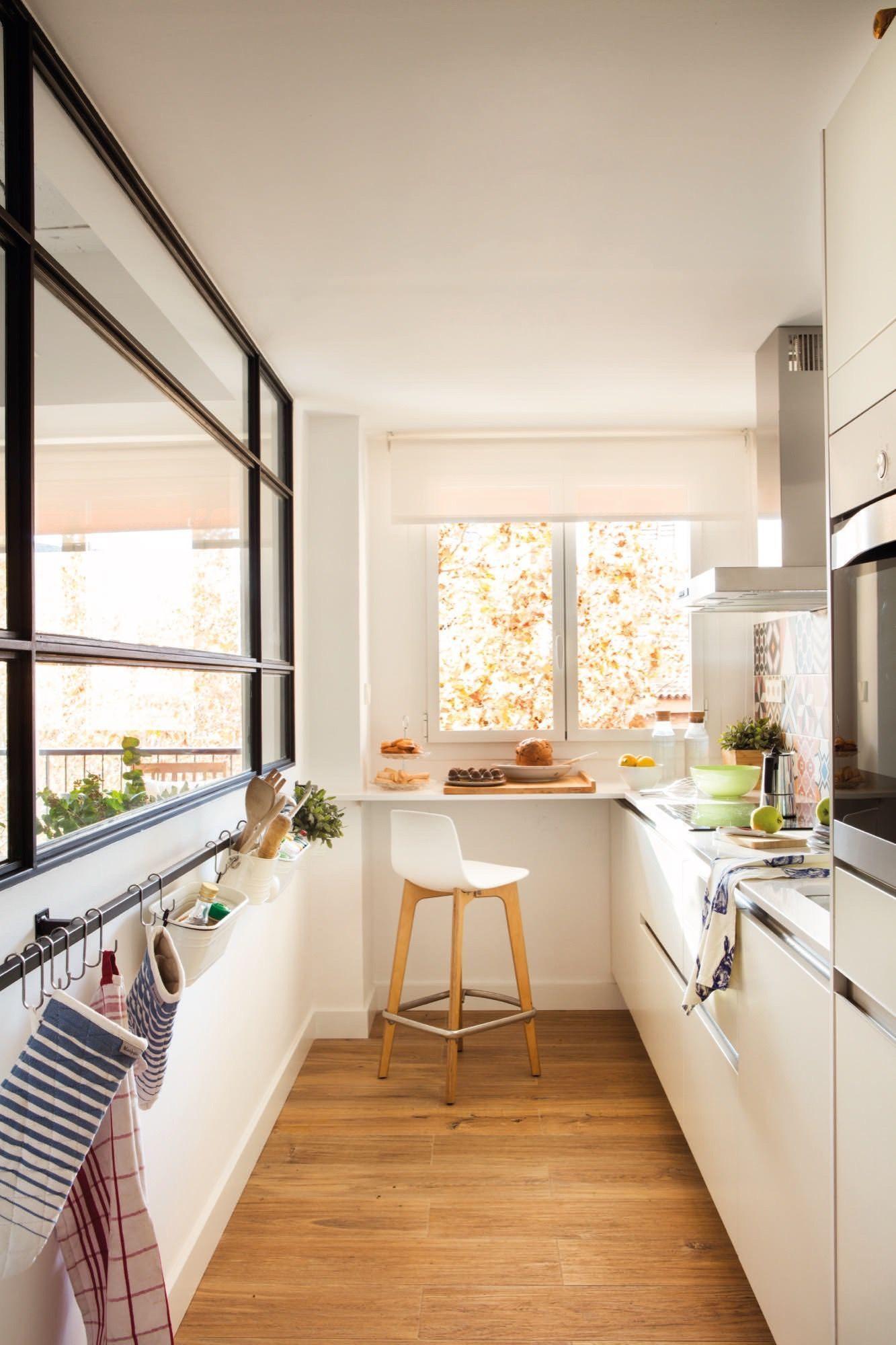 una cocina pequeña con barra de desayuno y ventana interior ...