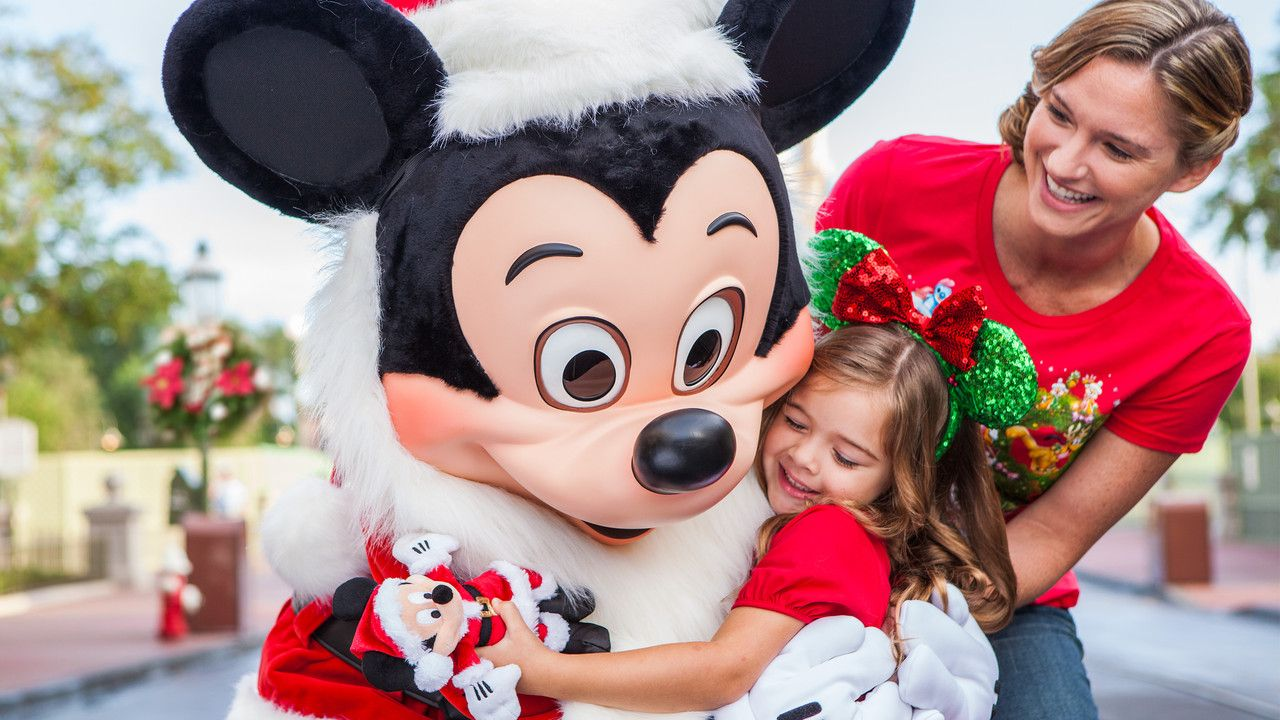 Mickey Mouse dressed up as Santa Claus hugging a young female Guest as her mother looks on in glee