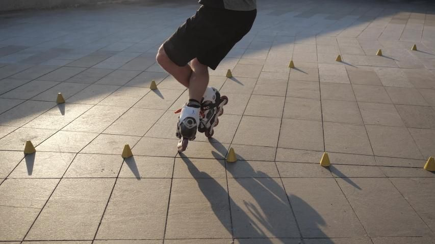 Ad: Close-up legs of a young man is professionally skating between cones on a nice evening sunset in a city park. Freestyle slalom Roller skating between cones.