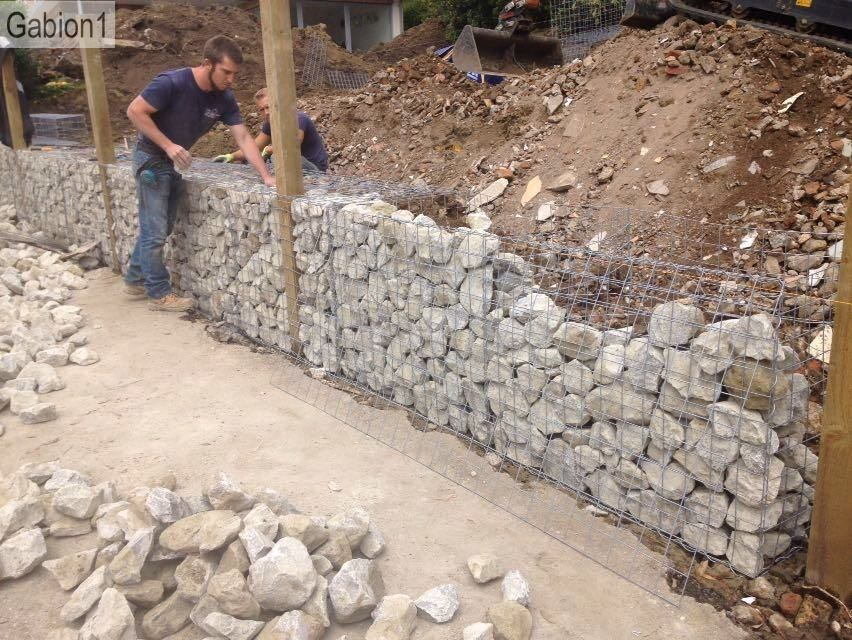 gabion wall construction, fence posts set between gabions