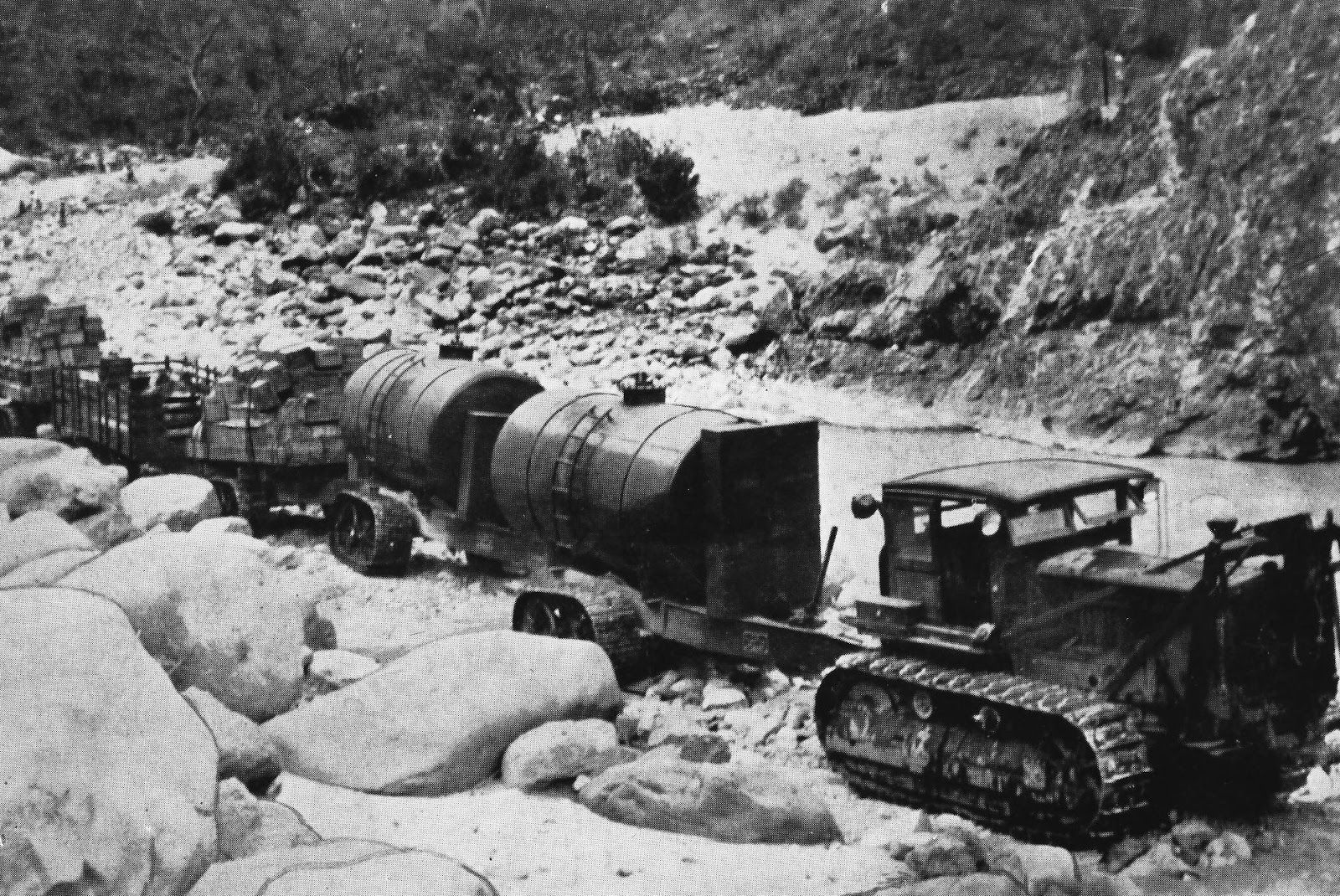 1939 version of a Caterpiller dozer with a cab and some kind of rack on the front.  The dozer is hauling several Athey trailer wagons carrying supplies to a mining camp far from roads or railroads.