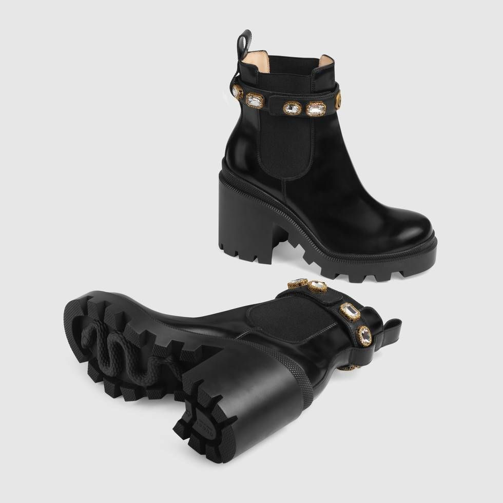 f77bd940f Shop the Leather ankle boot with belt by Gucci. The ankle boot in shiny  black leather is designed with a lug sole and elastic inserts on each side  for a ...
