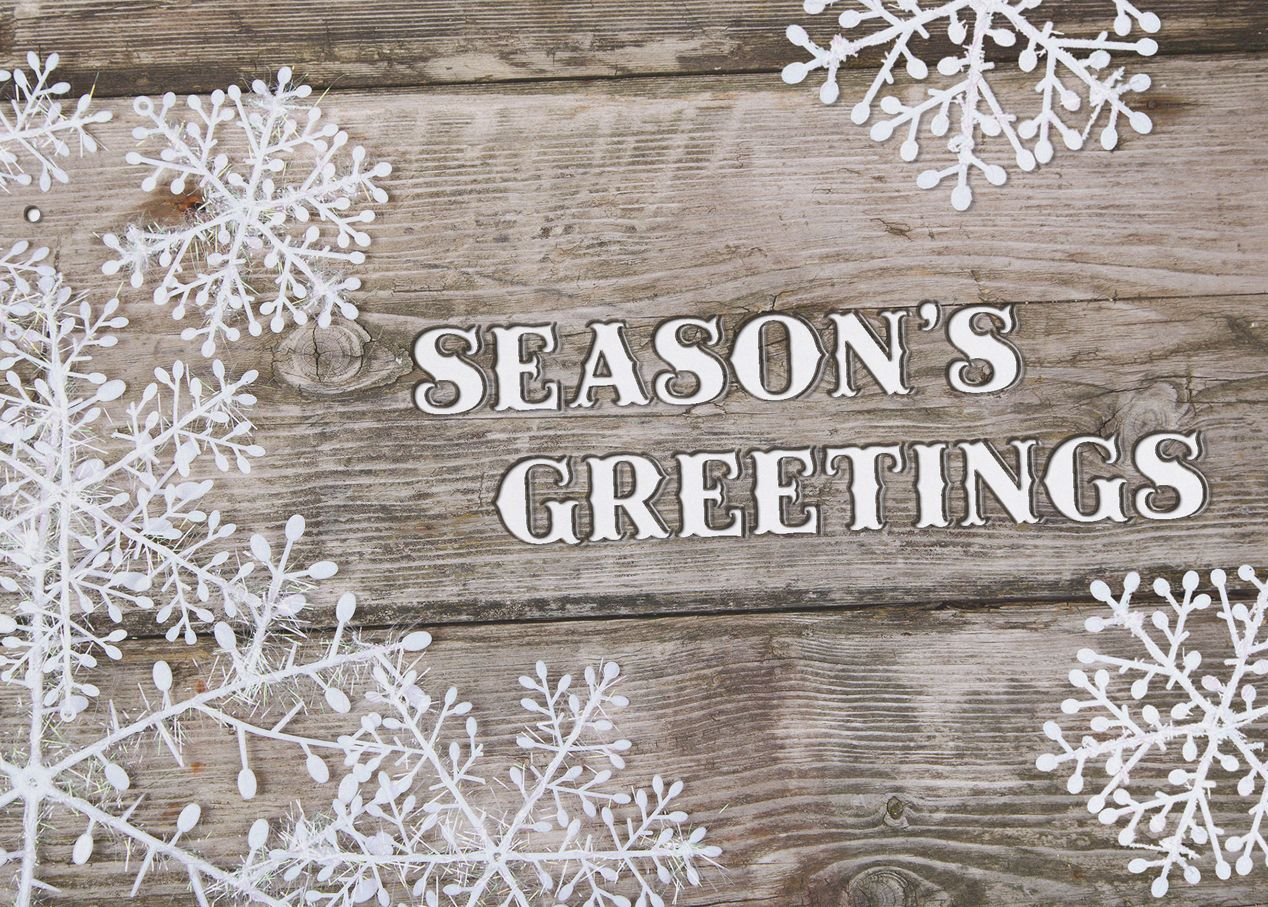Send rustic seasonal greetings with this holiday card with a wood grain and snowflake pattern.
