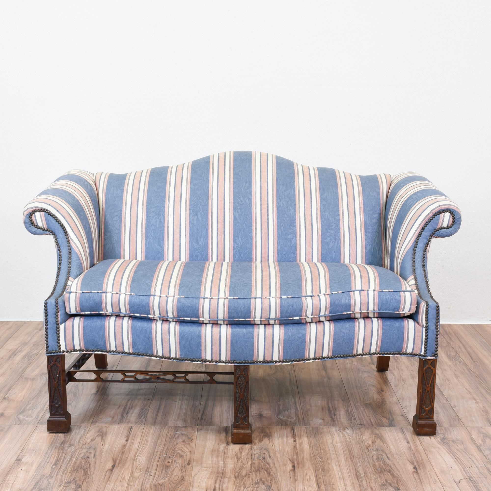 This camelback chippendale sofa is upholstered in a ...