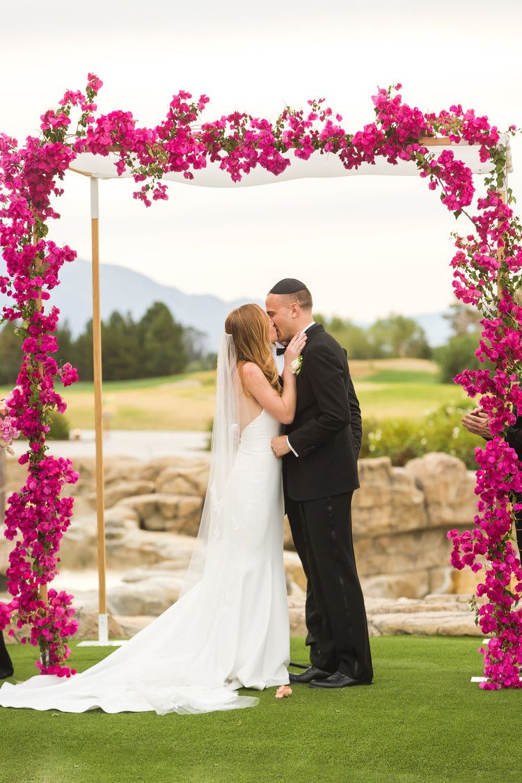 Classic Bride And Groom Kissing Under A Bougainvillea Chuppah At Their Palm Springs Jewish Wedding Wedding Plann Bougainvillea Wedding Wedding Jewish Wedding