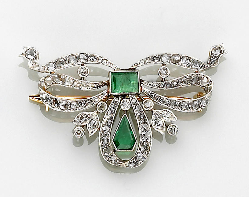 A belle èpoque emerald and diamond bow brooch, circa 1905  in the form of a bow, centering a rectangular-cut emerald and set with rose and old mine-cut diamonds, accented with a further kite-shaped emerald; mounted in platinum and eighteen karat gold.