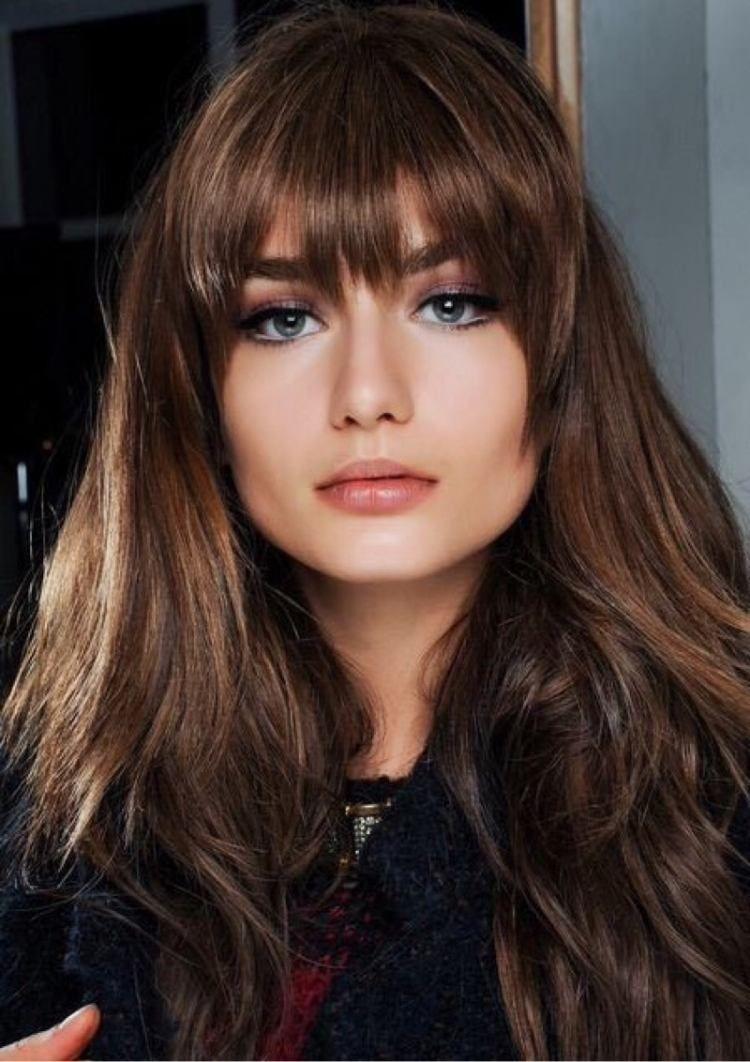 coiffure avec frange droite, cheveux longs bruns et balayage noisette
