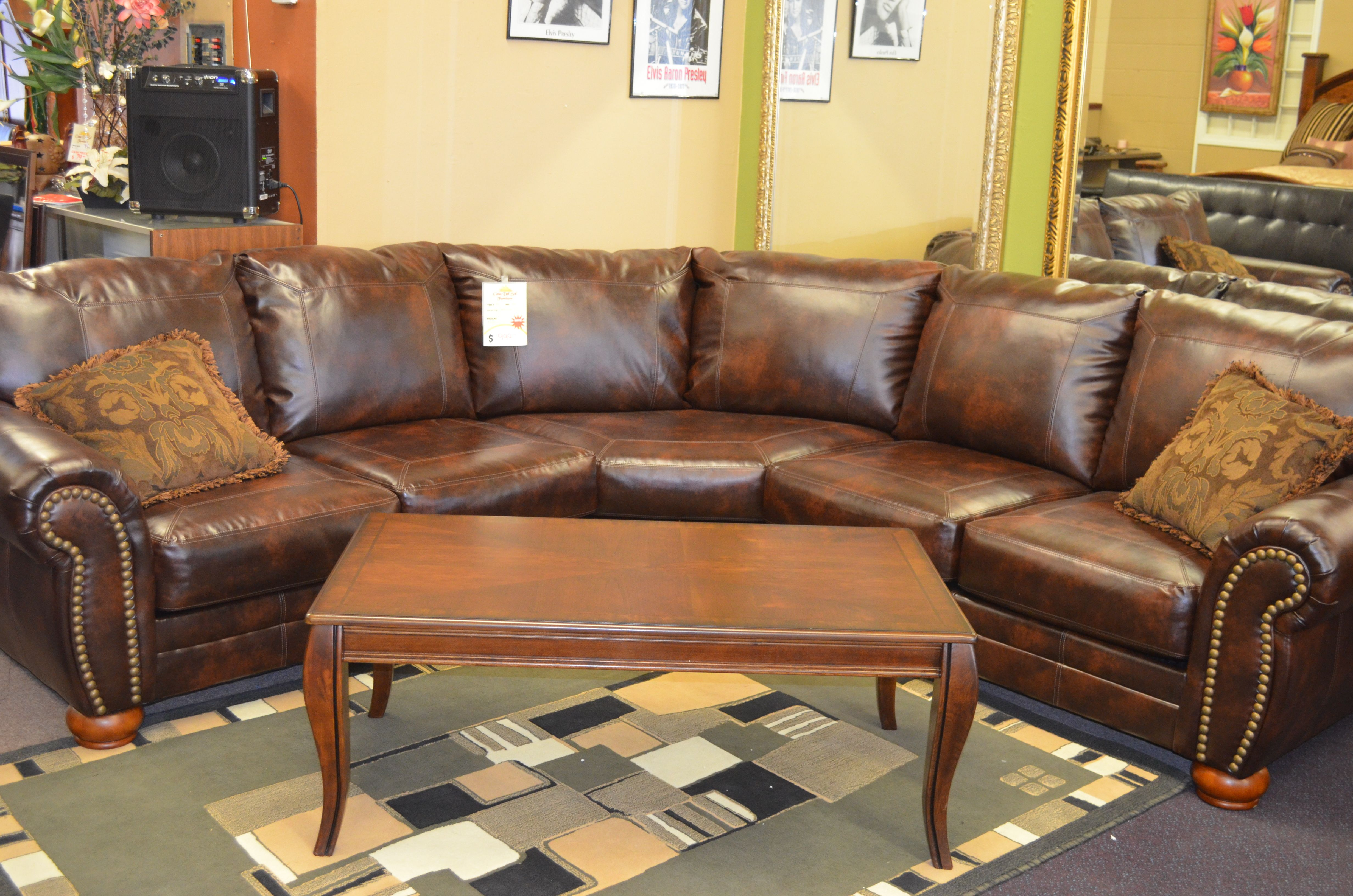 Bonded leather sectional with decorative nail heads on the front of ...