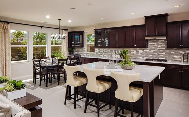Stainless steel appliances, food preparation island, granite countertops and maple cabinets outfit the kitchen. - Residence 2 at Carmel at Heritage Lake in Menifee, CA