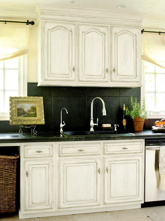 Beautiful distressed cabinetry with bold black counters and backsplash