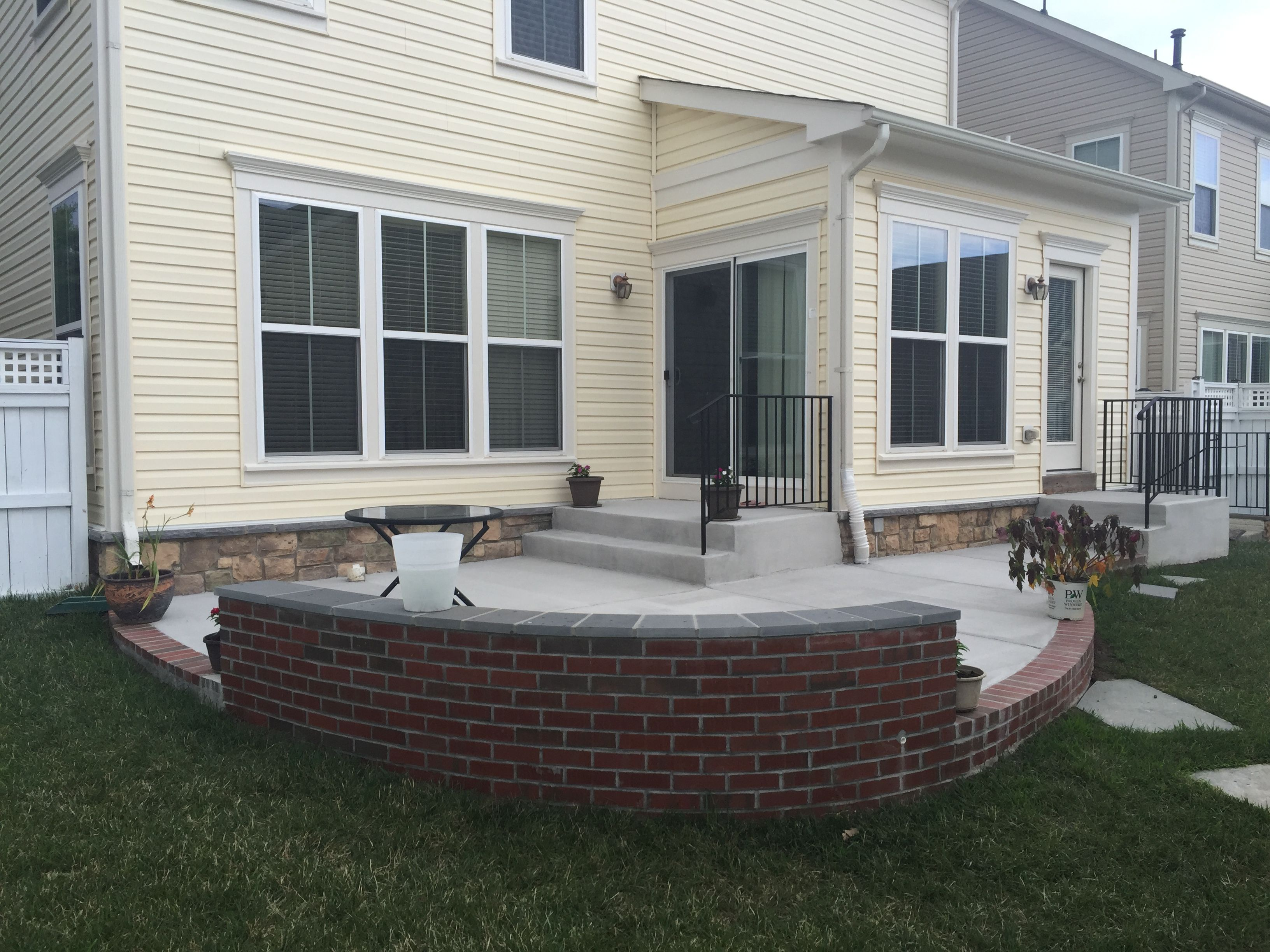 Concrete Patio With A Brick Seating Wall And Border In