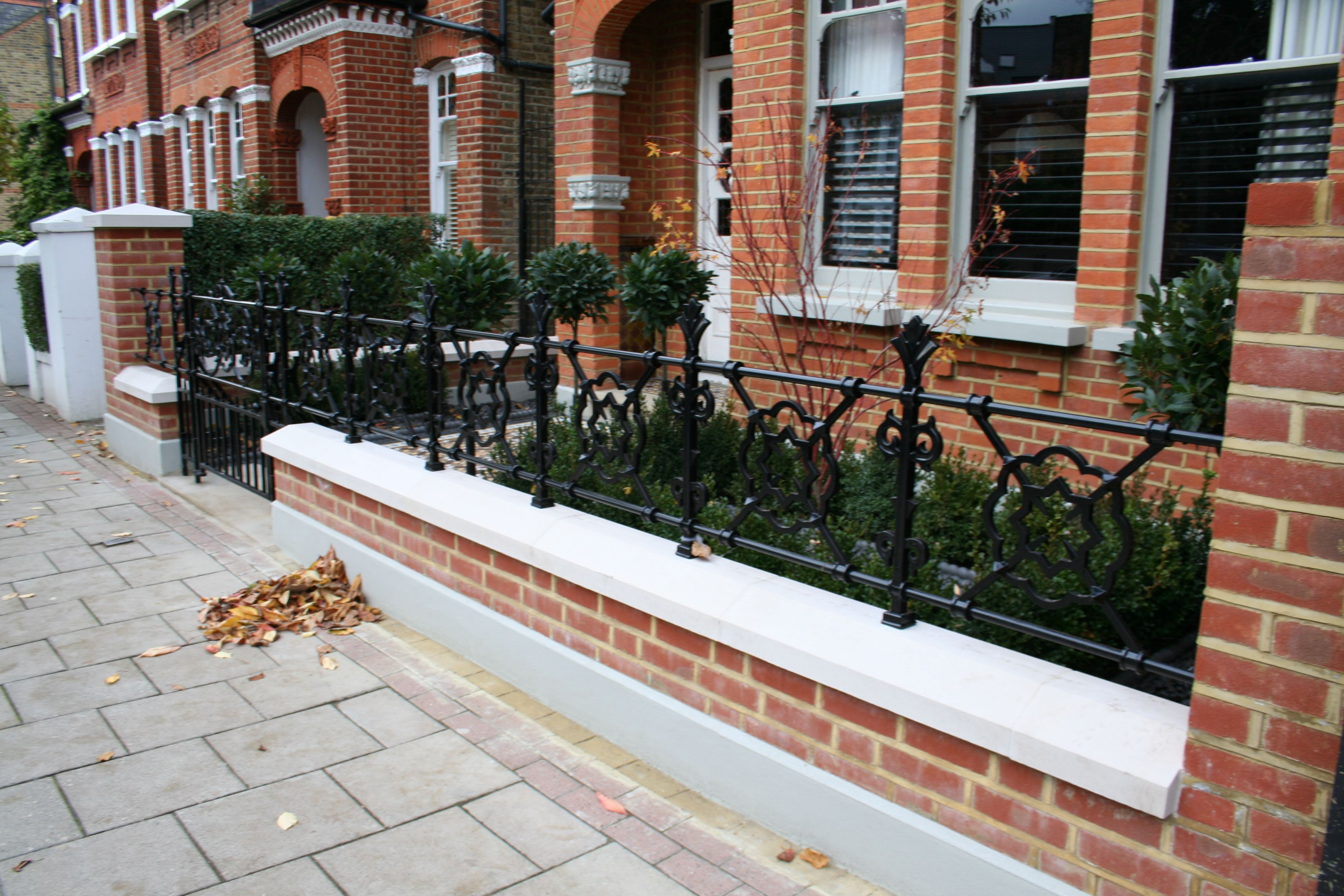 Stylish red brick wall and black railings in London front