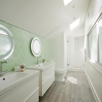 Web Photo Gallery Fabulous galley bathroom features separate side by side floating washstands and round vanity mirrors lining a wall clad in a green Moroccan tile backsplash