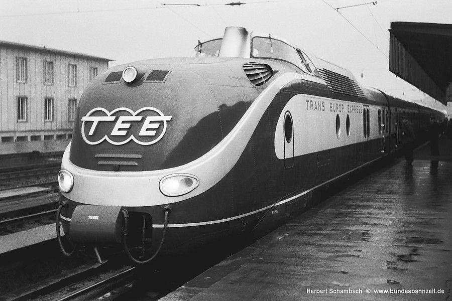 """Zum Fahrplanwechsel am 02.06.57 wird grenzüberschreitend das Top-Angebot im europäischen Fernverkehr eingeführt - der Trans Europ Express. Die DB stellte dafür mit den neu entwickelten Dieseltriebzügen der Baureihe VT11.5 die im internationalen Vergleich modernsten und komfortabelsten Fahrzeuge auf die Schienen.Noch brandneu, ist VT11 5 002 als TEE74 """"Saphir"""" nach Oostende denn auch bei regnerischem Wetter dem Fotografen eine Aufnahme wert; 28.07.57."""