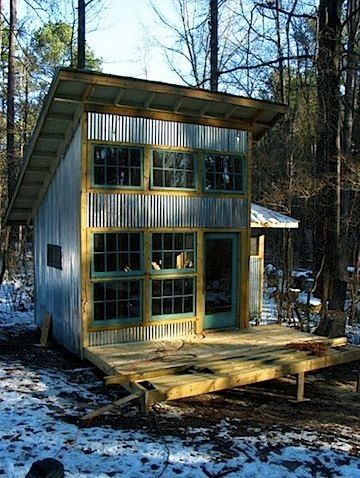 Two story tiny house with corrugated galvanized siding and green