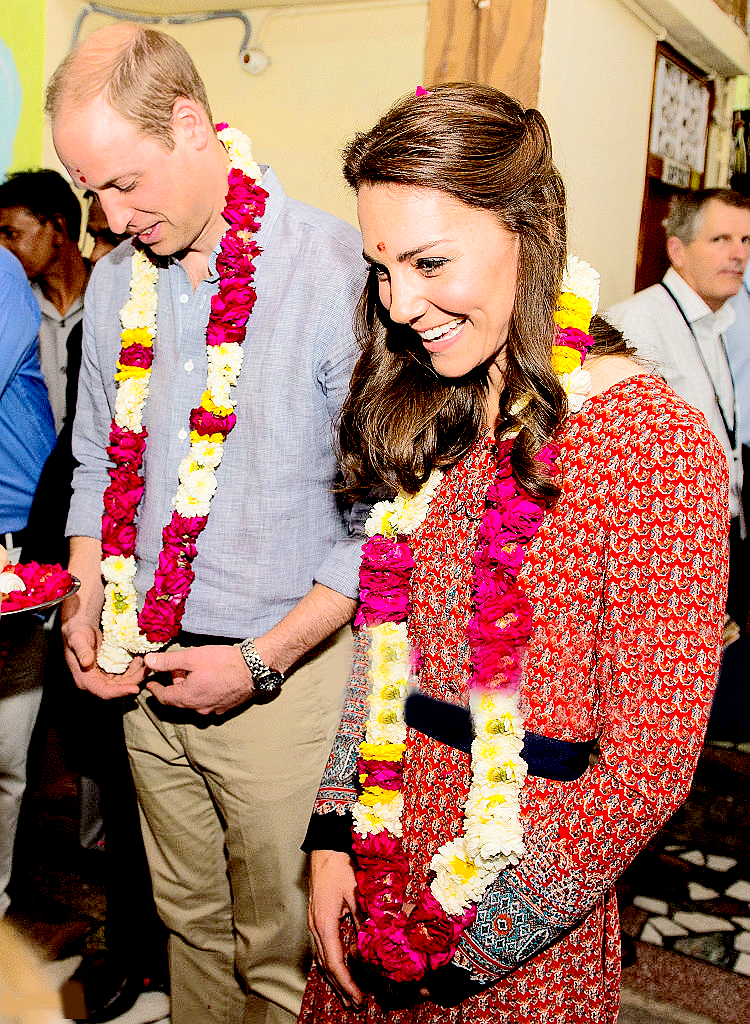 Catherine, Duchess of Cambridge and Prince William, Duke of Cambridge are greeted with garlands at a contact centre run by the charity Salaam Baalak