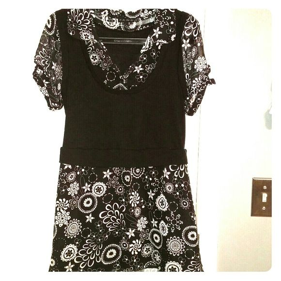 Women's vest top Black and white floral print. Sheer material with a solid looking vest. All one piece and button sleeve. Tops