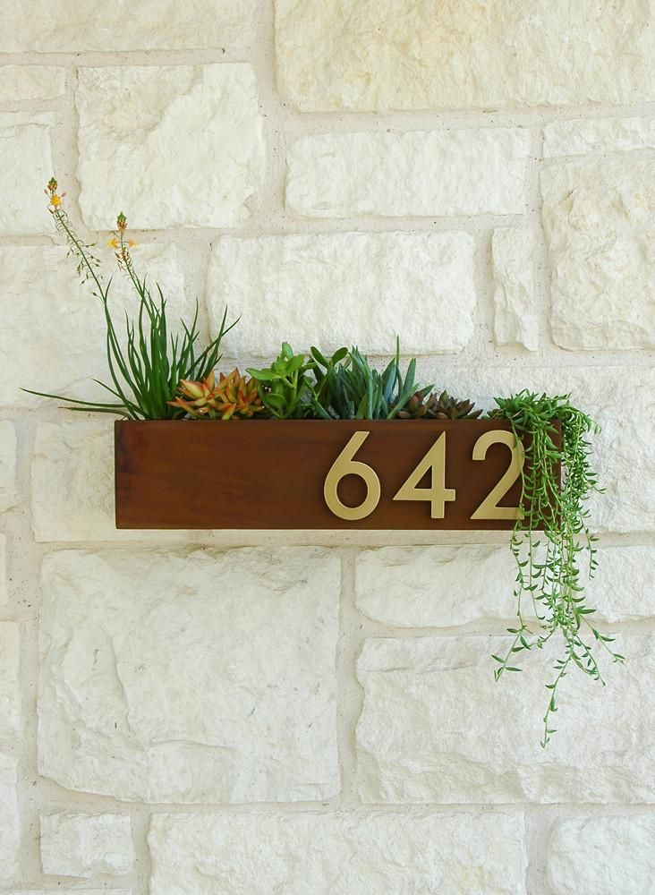 Silver or Brass Numbers is part of House numbers diy, Home entrance decor, House numbers, Name plates for home, House number sign, Entrance decor - Welcome Home  This modern wall planter adds flair and style to the facade of your home with magnetic aluminum address numbers  Looks particularly great with colorful succulents! This planter is made to order in Austin, TX and is constructed of 14 gauge steel  The planter floats about a quarter inch off the wall and is held with a handmade metal cleat (included) for ease of hanging  Each planter has a welded 'lip' on the back so it easily slides into the custom metal cleat  4  solid aluminum numbers are included and come with industrial strength magnets attached(aka rare earth or neodymium magnets)  They are easy to hang and adjust, will stay put, and in case you move you can take your planter and simply order new numbers! Available finishes and fonts Our numbers have been powder coated for extra durability and longevity  They are available in silver with a clean, modernfont or in brass (gold tone) with a midcentury style font  Dimensions Overall 20 W x 5 H x 4 D Street Numbers 4 H Succulents not included Neodymium magnets should be handled with care  They can damage electronics and interfere with pace makers