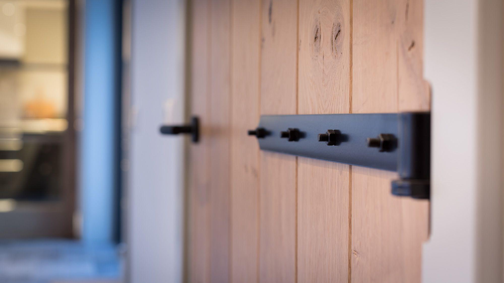 Strakke eikenhouten Maetwerck deuren inclusief smeedijzerzwart deurbeslag.