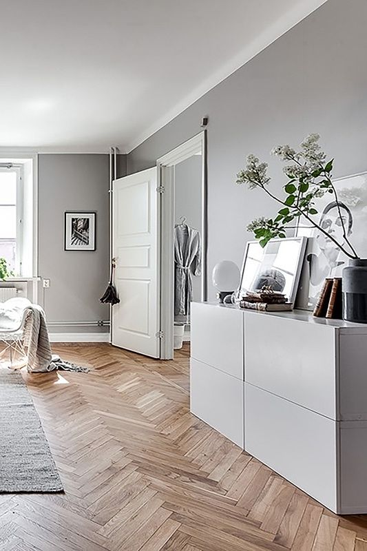 Beautiful living room with a herringbone parquet and a white cupboard. We love the mix of white and grey. If you want to know how to deal with challenging conditions, check out our blogpost!