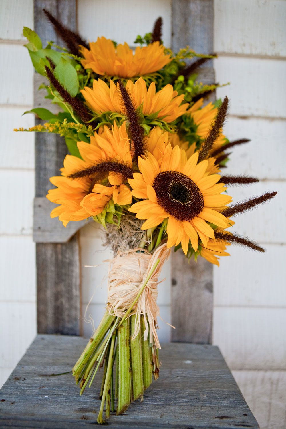 A rustic barn wedding bouquet of bright sunflowers at the Historic Barns of Nipmoose. Photography by Tracey Buyce