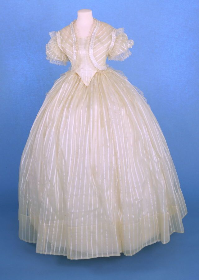 Wedding dress: fichu (with a: bodice, b: skirt a) Date: 1864 Media: Satin Stripe Silk Organza And Taffeta Country: United States Accession Number: 59.21.1c Bolero like fichu, tied at back and trimmed with white silk ruching and lace.