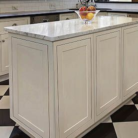 center island in white cabinets with decorative door panels on ...